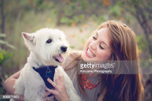 Female holding West Highland White Terrier