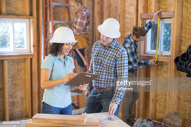 Female homeowner going over building plans with construction worker
