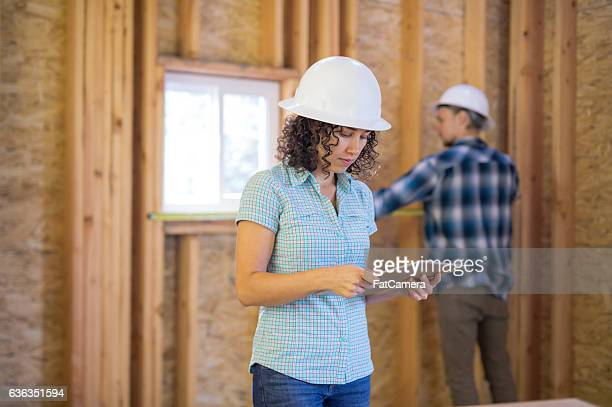 Female homeowner going over house building plans on