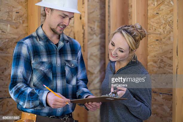 Female homeowner going over house building plans with contractor