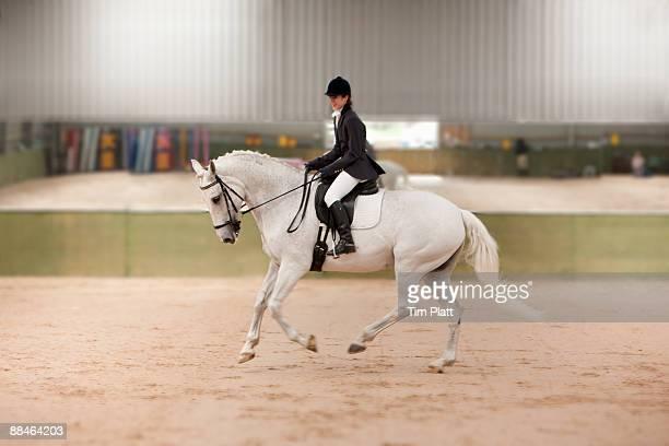 Female horse rider practising dressage.