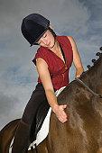 Female horseback rider stroking horse