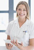 Female hospital worker holding clipboard, smiling