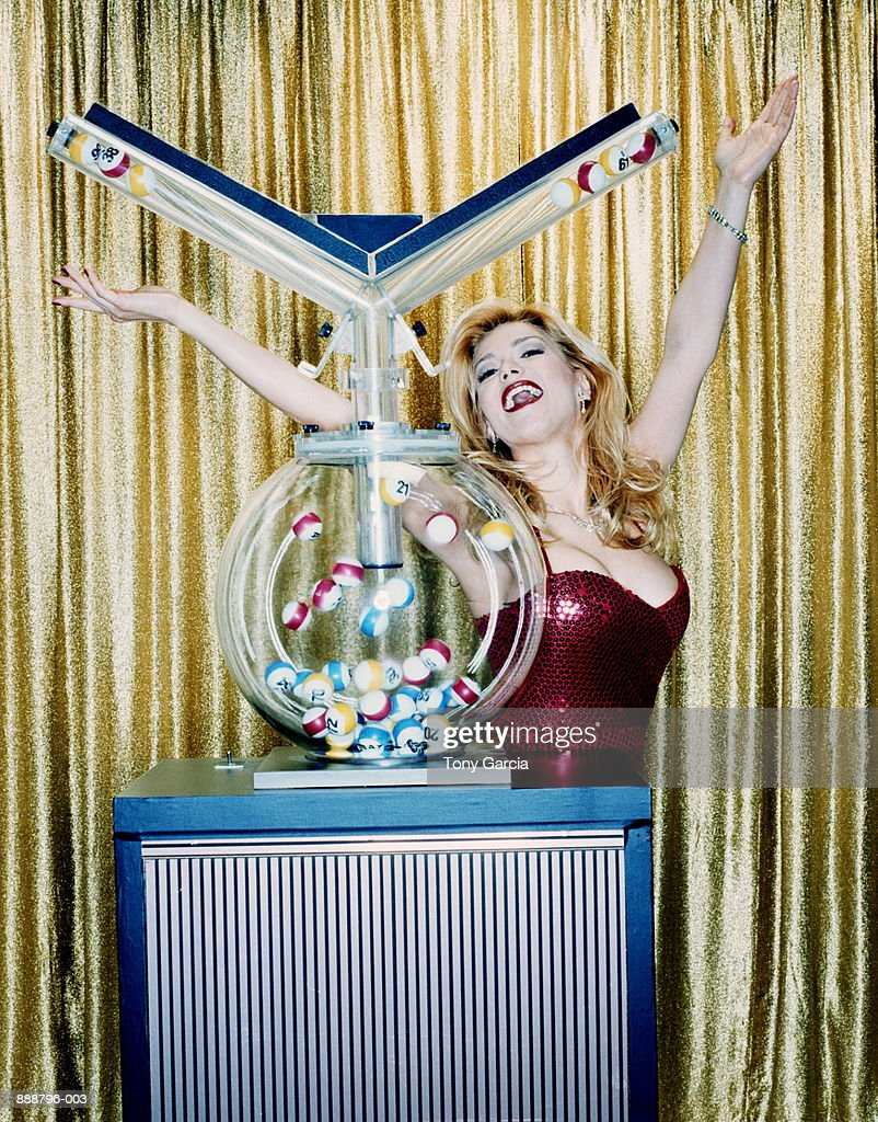 Female host raising arms beside lottery machine (cross-processed)