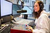 Female host using music mixer while wearing headphones at radio station