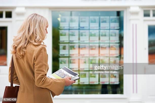Female house buyer outside estate agents window