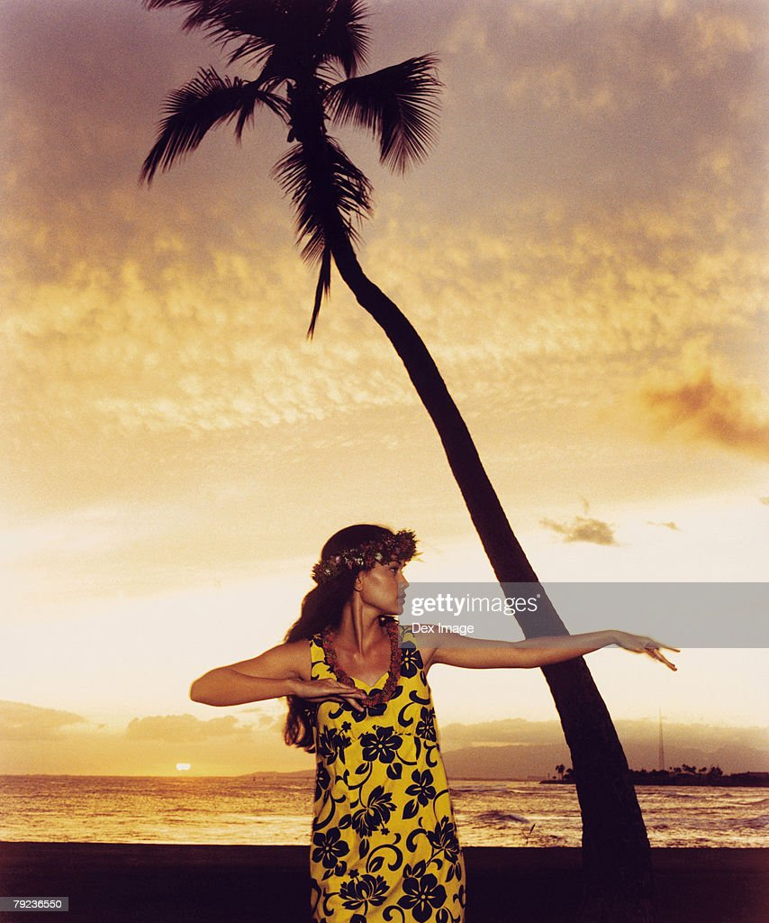 A female hula dancing outdoors near the ocean at sunset : Stock Photo