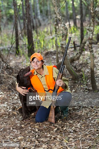 Female hunter in woods with labrador retriever