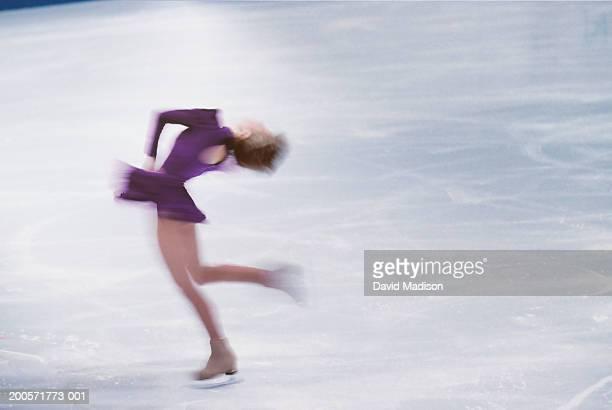 Female ice skater spinning on ice