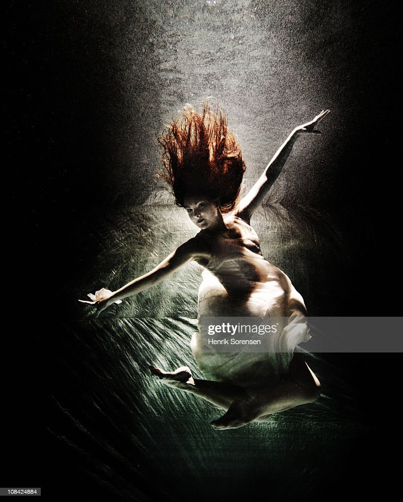 Female in an evening dress sinking under water : Stock Photo