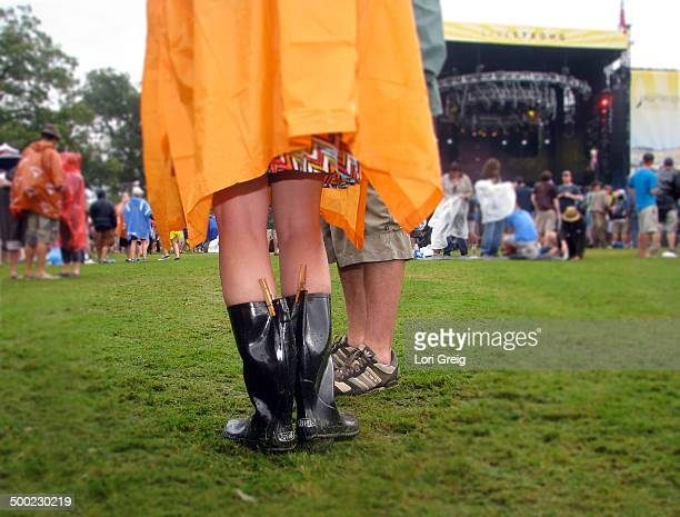 Female in orange poncho and rain boots with clothespins at Austin City Limits music festival