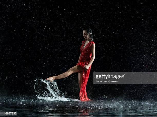 Female in red, foot splashing in water, night