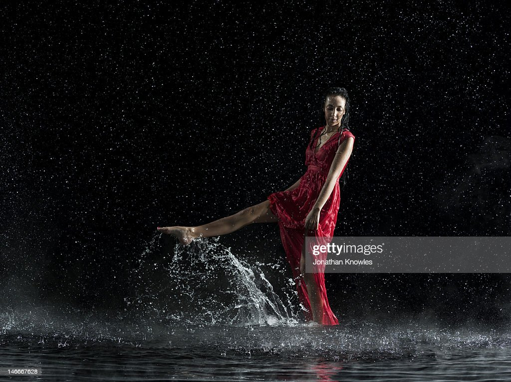 Female in red in water, rainy night : Stock Photo