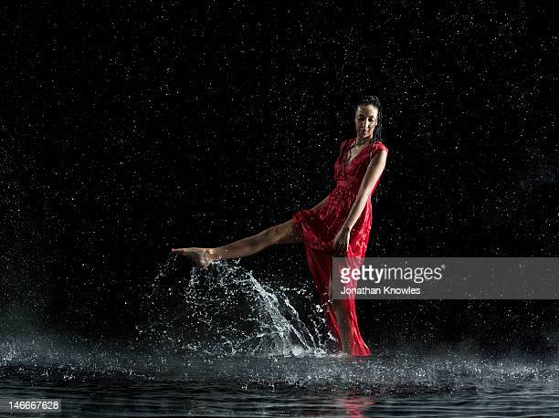 Female in red in water, rainy night