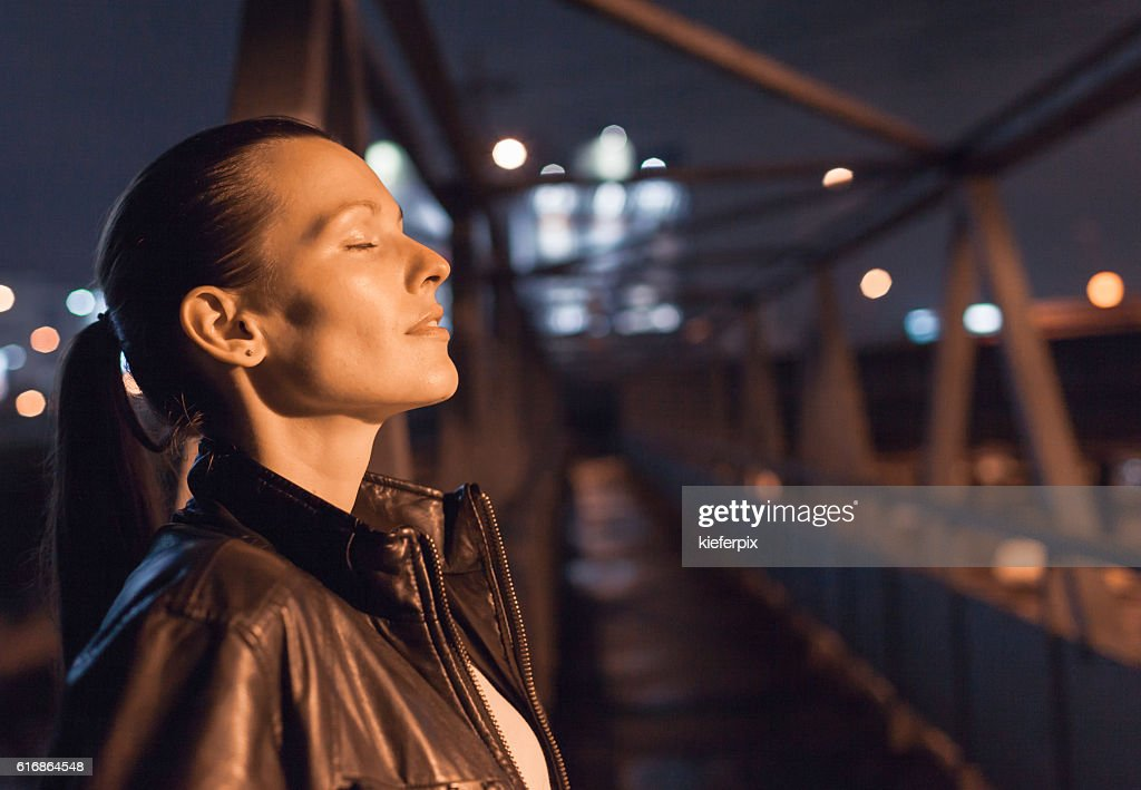 Female in the city feeling relaxed with her eyes closed. : Stock Photo