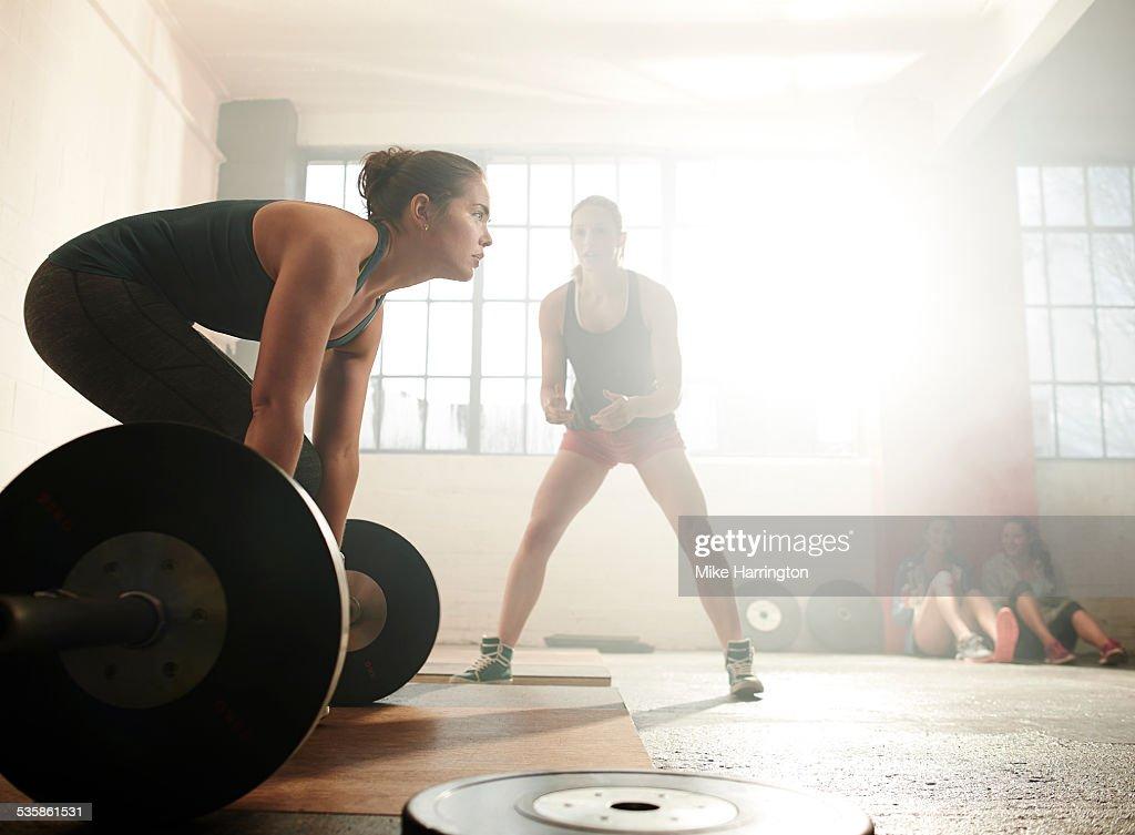 Female in warehouse gym, preparing for deadlift