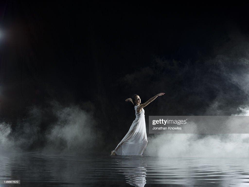 Female in white dancing in water, misty night