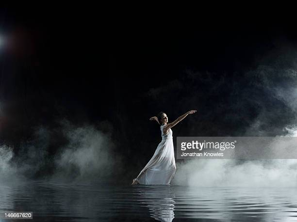 Female in white dancing in water, misty night