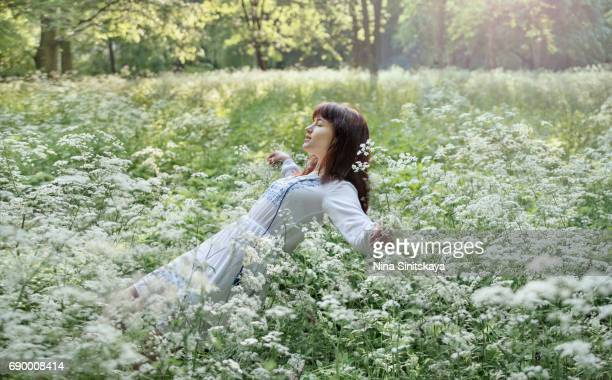 Female in white dress falling into white flowers, outdoors