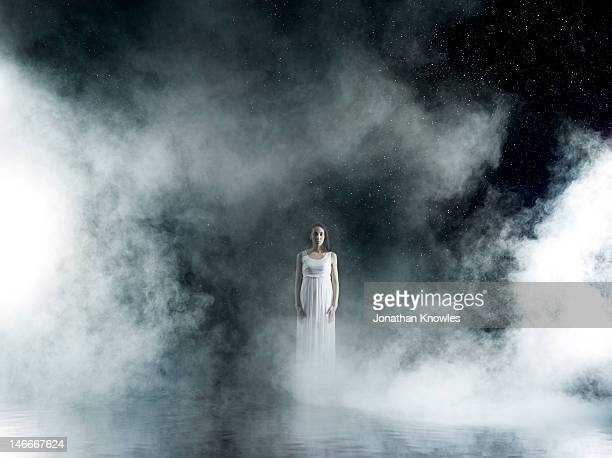 Female in white in rain,  misty night