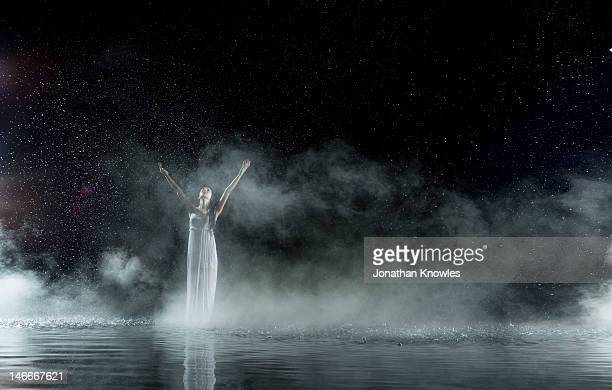 Female in white in water, rainy night