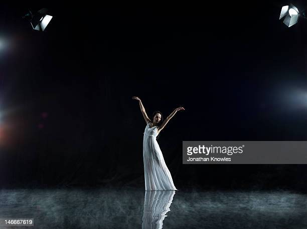 Female in white in water,dance pose,  misty night