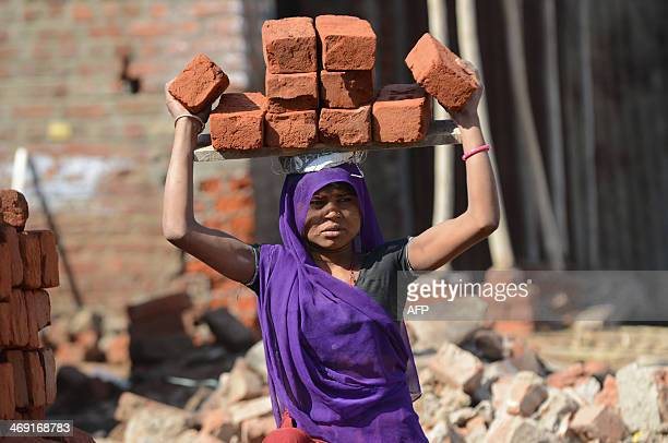 A female Indian labourer lifts bricks over her head at a construction site at Adalaj village some 35 kms from Ahmedabad on February 13 2014 India's...