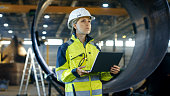 Female Industrial Engineer in the Hard Hat Uses Laptop Computer while Standing in the Heavy Industry Manufacturing Factory. In the Background Various Metalwork Project Parts Lying