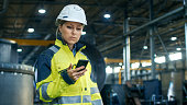 Female Industrial Worker in the Hard Hat Uses Mobile Phone While Walking Through Heavy Industry Manufacturing Factory. In the Background Various Metalwork Project Parts Lying