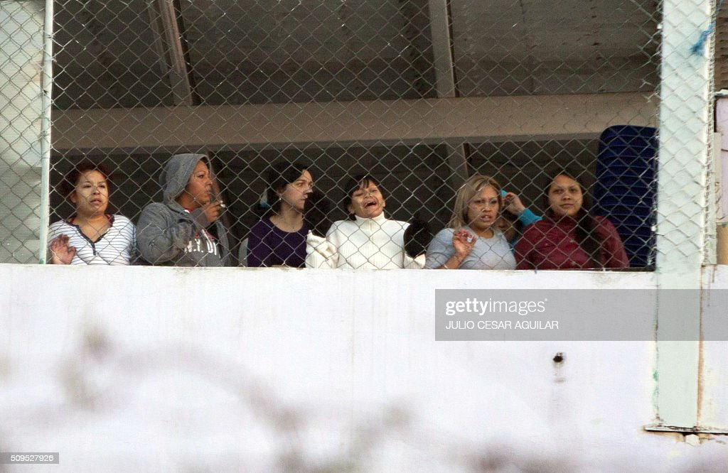 Female inmates look to the street from the Topo Chico prison in the northern city of Monterrey in Mexico where according to local media at least 30 people died in a prison riot on February 11, 2016. Riot police and ambulances were deployed at the Topo Chico prison as smoke billowed from the facility. Broadcaster Televisa reported that 30 died while Milenio television spoke of 50 victims, with inmates and prison guards among them. AFP PHOTO / JULIO CESAR AGUILAR / AFP / Julio Cesar Aguilar