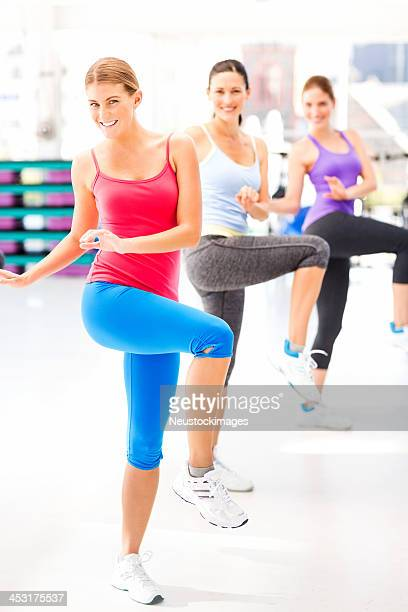 Female Instructor And Customers Practicing Aerobic Dance In Gym