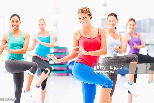Female Instructor And Fitness Class Practicing Aerobic Dance In Gym