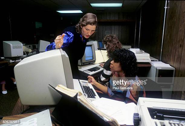 A female instructor goes over a lesson with a female student during an early computer class Chicago Illinois mid 1980s