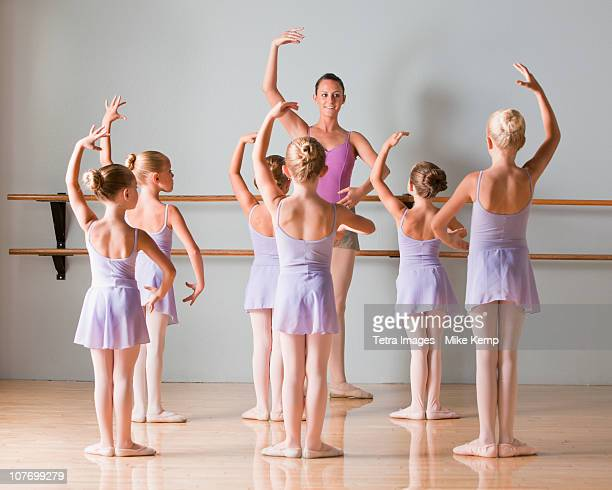 Female instructor training ballet dancers (6-7,8-9) in dance studio