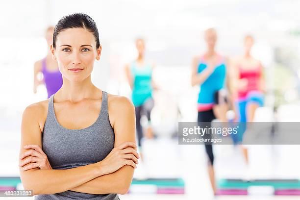 Istruttore di sesso femminile con i clienti esercizio fisico all'Health Club