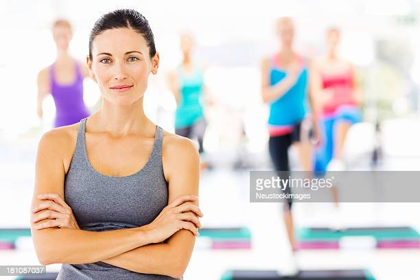 Female Instructor With Fitness Class At Health Club