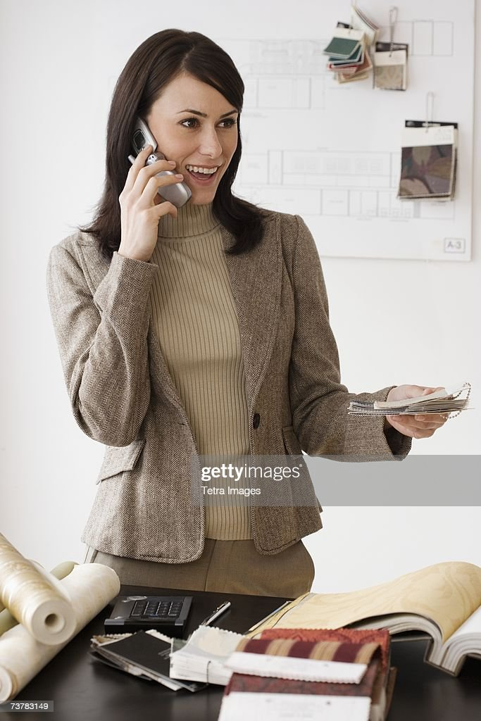 Female Interior Designer Talking On Cell Phone Stock Photo