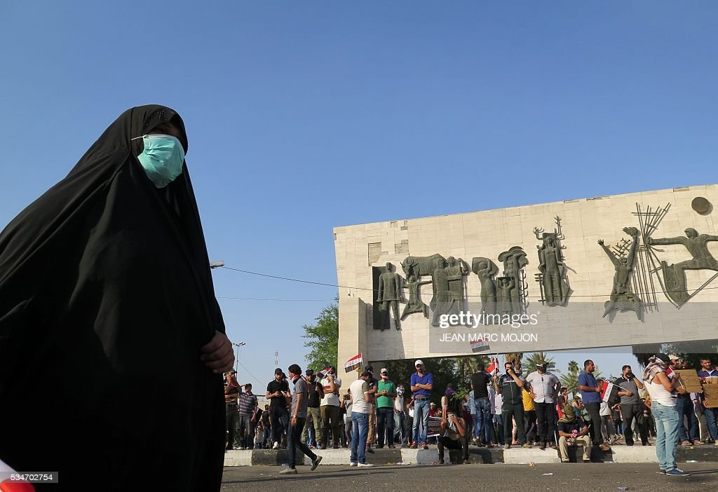 A female Iraqi protester wearing a surgical mask attends a demonstration at Tahrir square in Baghdad on May 27, 2016 defying a call by Iraqi prime minister to halt protests while security forces are battling the Islamic State group in Fallujah. Security forces fired tear gas as thousands of protesters gathered in central Baghdad and attempted to head to the Green Zone, a fortified area they have breached twice in the last month. / AFP / Jean Marc MOJON