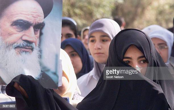 A female Iraqi student carries a portrait of former Iranian Shia leader Grand Ayatolla Khomeini during a march to protest the recently signed Iraqi...