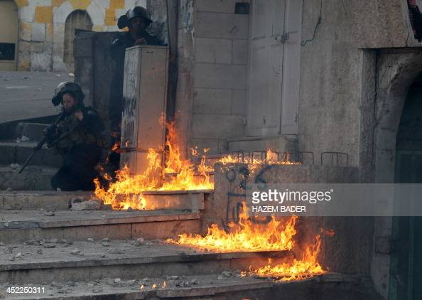 A female Israeli border guard reacts after a petrol bomb thrown by Palestinian demonstrators landed next to her in the West Bank city of Hebron...