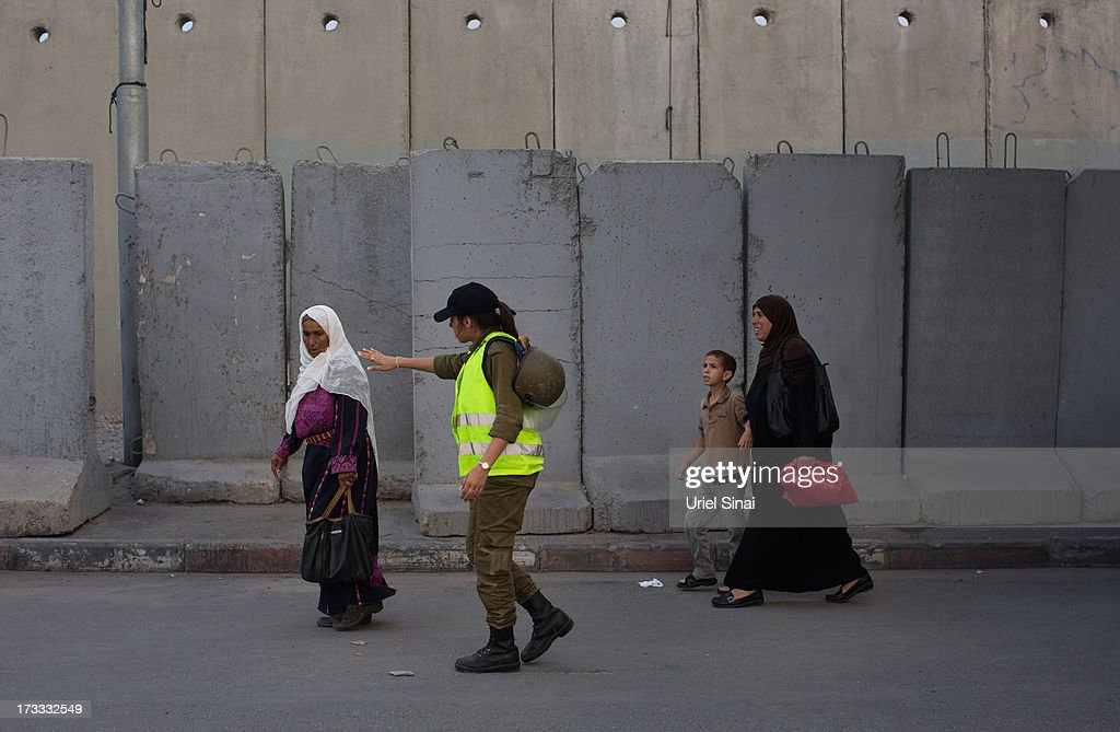 A female Israeli soldier calls a Palestinian Muslim worshipper for inspection as she crosses the Qalandia checkpoint on her way to Jerusalem on July 12, 2013 near Ramallah, West Bank. Thousands of Palestinian worshippers crossed from the West Bank into Israel to attend the first Friday prayers of Ramadan at the the Al-Aqsa mosque compound in Jerusalem. Ê