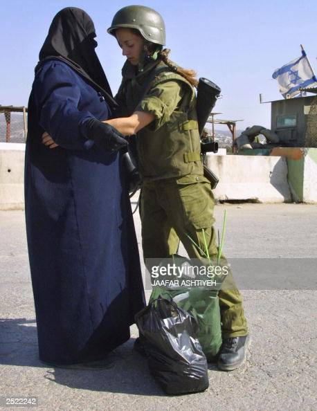 A female Israeli soldier frisks a fundamentalist Muslim Palestinian woman at the West Bank checkpoint of Hawara south of Nablus 22 September 2003...