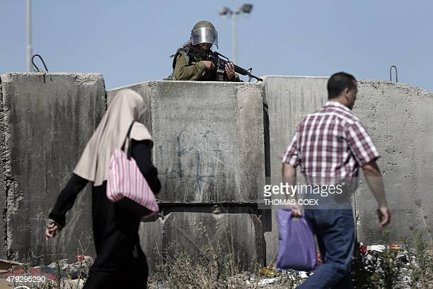 A female Israeli soldier stands guard at the Qalandia checkpoint south of Ramallah as thousands of Palestinians wait to cross from the West Bank to...