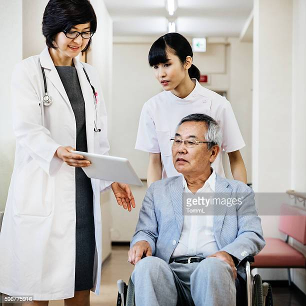 Female japanese doctor showing Data on Digital Tablet