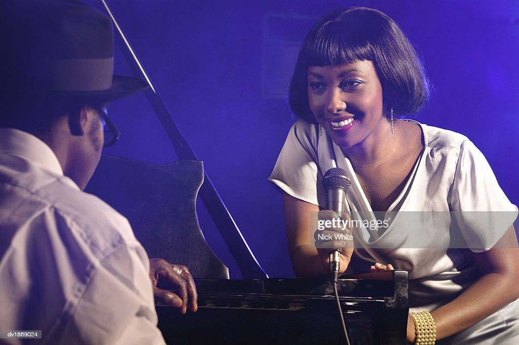 Female Jazz Singer Leaning on a Grand Piano : Stock Photo