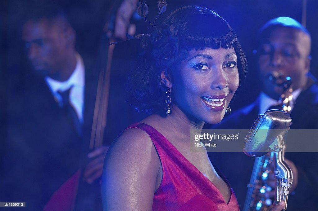 Female Jazz Singer Performs by a Retro Microphone, Jazz Band in the Background : Stock Photo