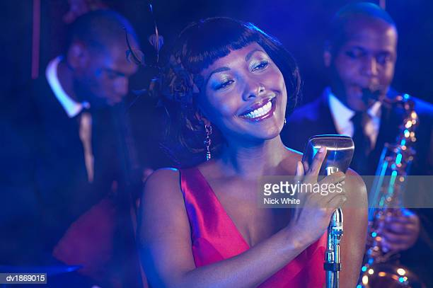 Female Jazz Singer Performs by a Retro Microphone, Jazz Band in the Background