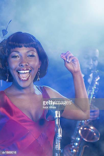 Female Jazz Singer Performs by a Retro Microphone, Saxophonist in the Background