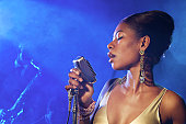 Female Jazz Singer Standing With a Microphone in Front of a Man Playing an Alto Saxophone