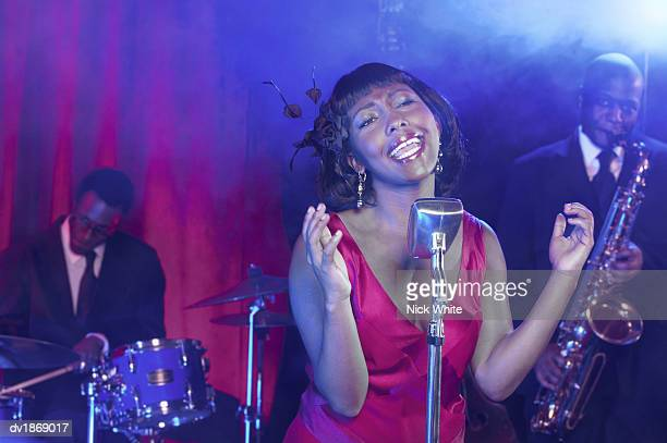 Female Jazz Singer Stands by a Retro Microphone, Performing With Passion, a Saxophonist and Drummer in the Background